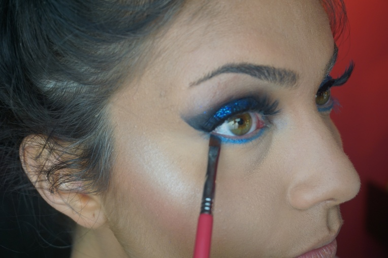 Over the matte blue shade, apply a blue shimmery shadow